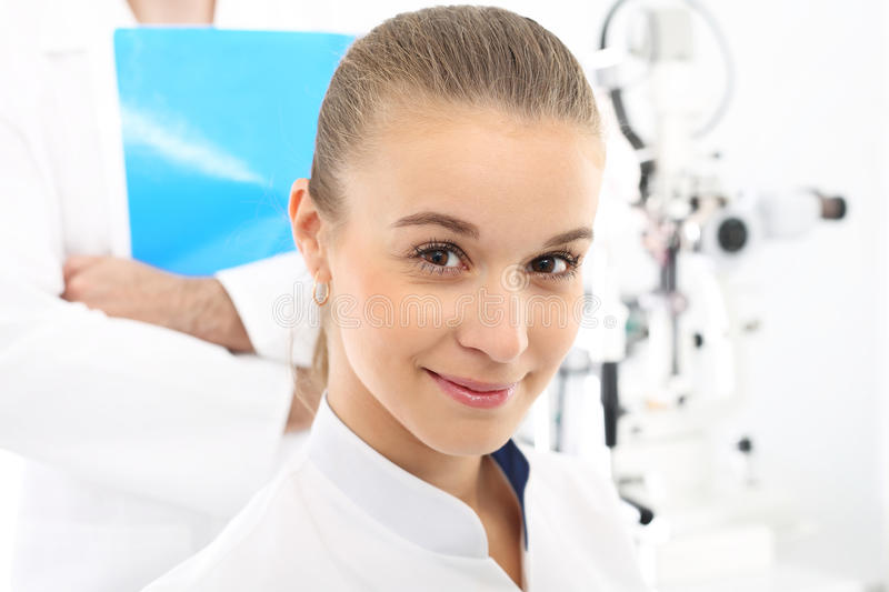 A student of medicine at practice. Young attractive doctor ophthalmologist at an ophthalmologist stock images