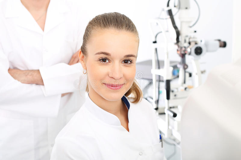 A student of medicine at practice. Young attractive doctor ophthalmologist at an ophthalmologist stock photo