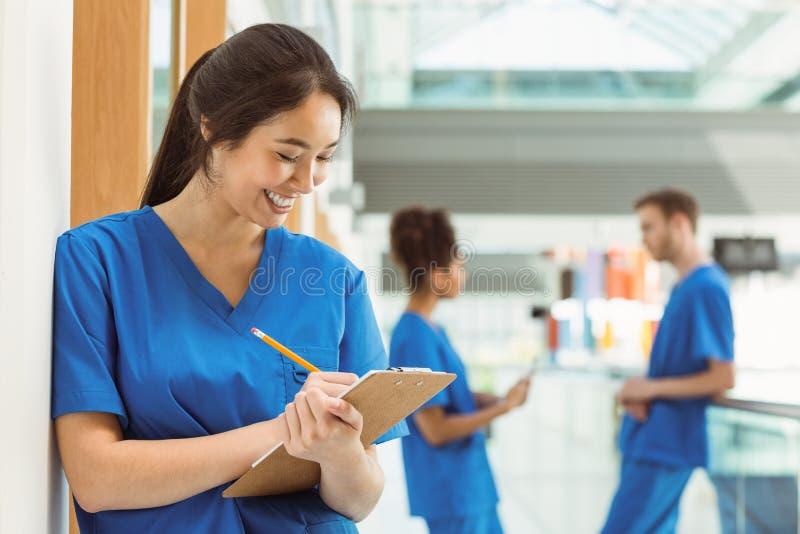 Student medycyny bierze notatki w korytarzu obraz stock