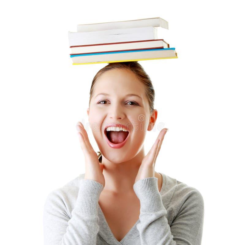 Student met boeken op haar hoofd stock foto