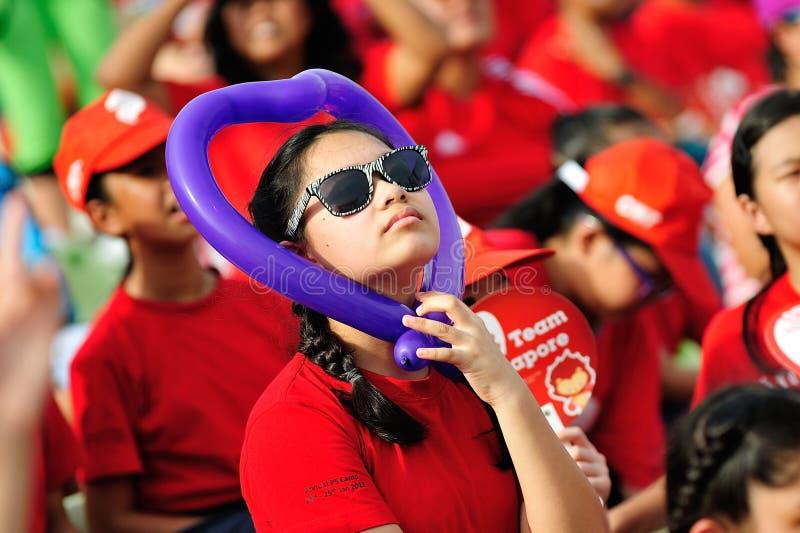Student met een ballon die van de hartvorm Repetitie 2013 de Nationale van de Dagparade (NDP) bekijken royalty-vrije stock afbeeldingen