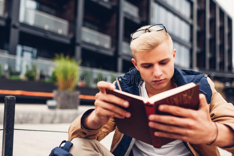 Student met het boek van de rugzaklezing het koelen door modern hotel op regenachtige de herfstdag royalty-vrije stock foto's