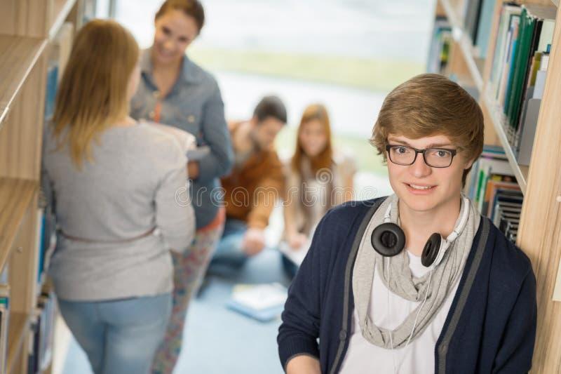 Student met hoofdtelefoons in bibliotheek stock fotografie