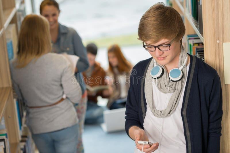 Student met hoofdtelefoons in universiteitsbibliotheek royalty-vrije stock fotografie