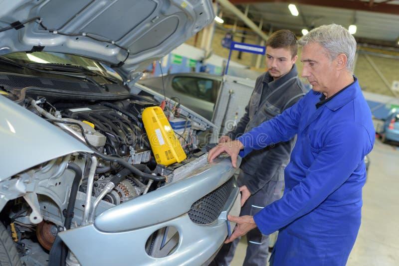 Student met instructeur die auto herstelt tijdens leertijd stock fotografie