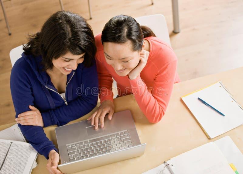 Student met laptop die thuiswerk met vriend doet stock foto's