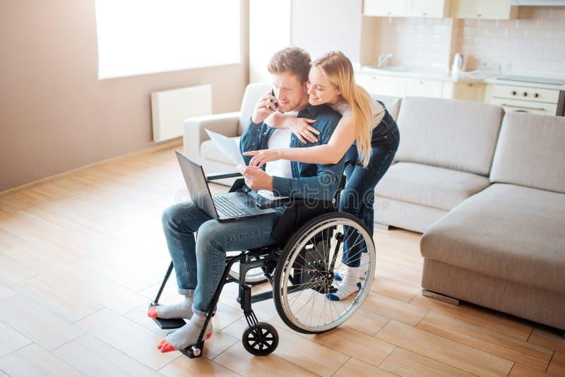 Student met onbekwaamheidszitting op rolstoel De vrolijke vrouwentribune erachter en omhelst hem Het kijken op laptop Jonge mens royalty-vrije stock afbeelding