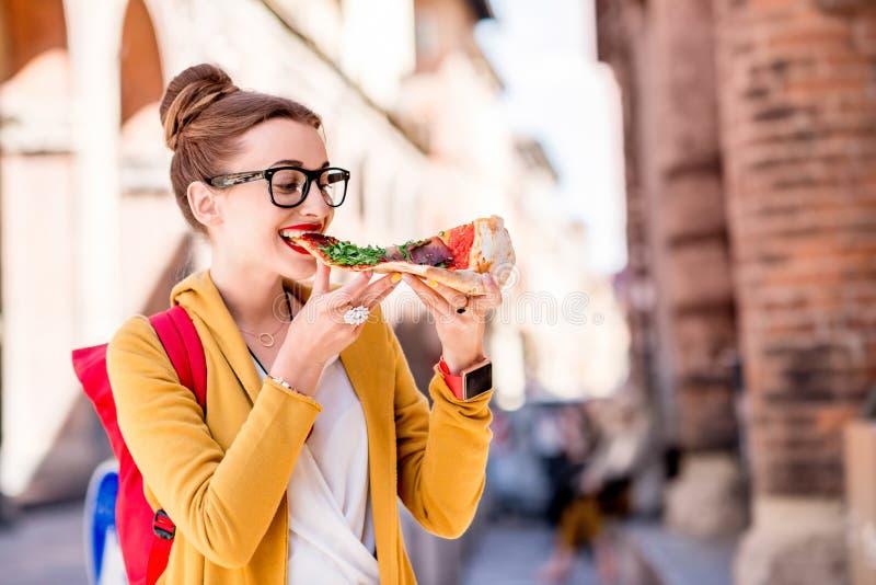 Student met pizza dichtbij de universiteit in de stad van Bologna stock foto's