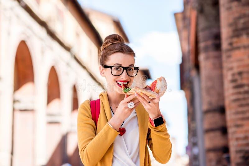 Student met pizza dichtbij de universiteit in de stad van Bologna royalty-vrije stock foto