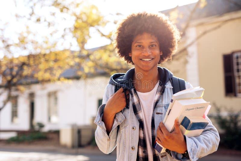 Student met veel boeken in universiteitscampus stock afbeeldingen
