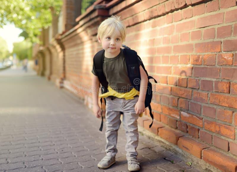 Student mit großem Rucksack nahe dem Schulgebäude Zurück zu Schule stockfotografie