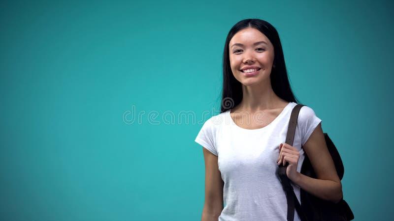 Student mit Rucksack lächelnd und Kamera, blauen Hintergrund, Statistik betrachtend lizenzfreies stockfoto