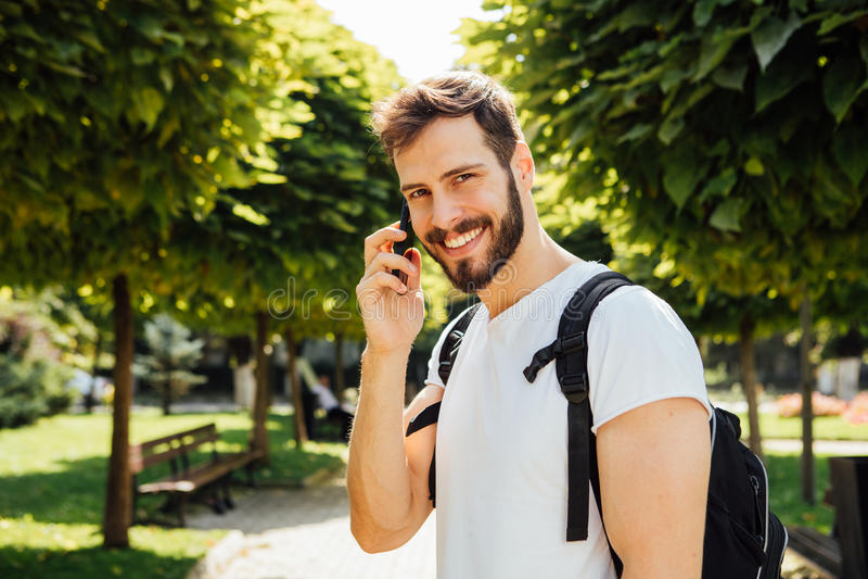 Student mit Rucksack sprechend am Mobiltelefon lizenzfreies stockbild