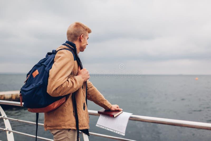 Student mit Rucksack und Buch gehend durch Meer nach Klassen und bewundern Ansicht über Strand in Odessa stockfoto