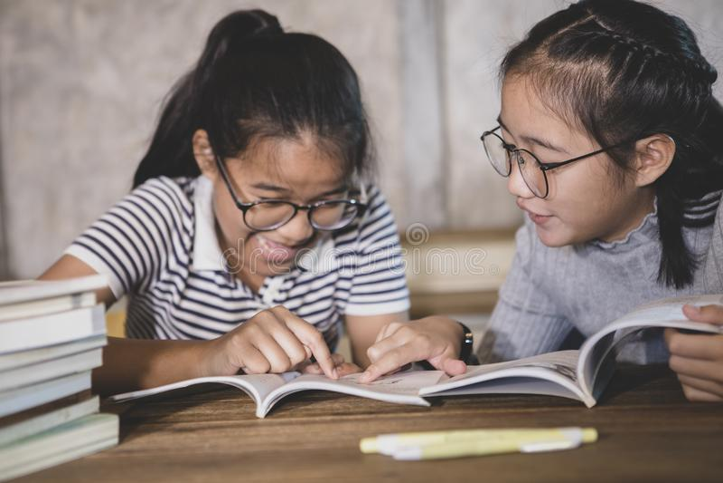 Student mit zwei Asiaten, der ein Schulbuch mit Glückgefühl liest stockbild