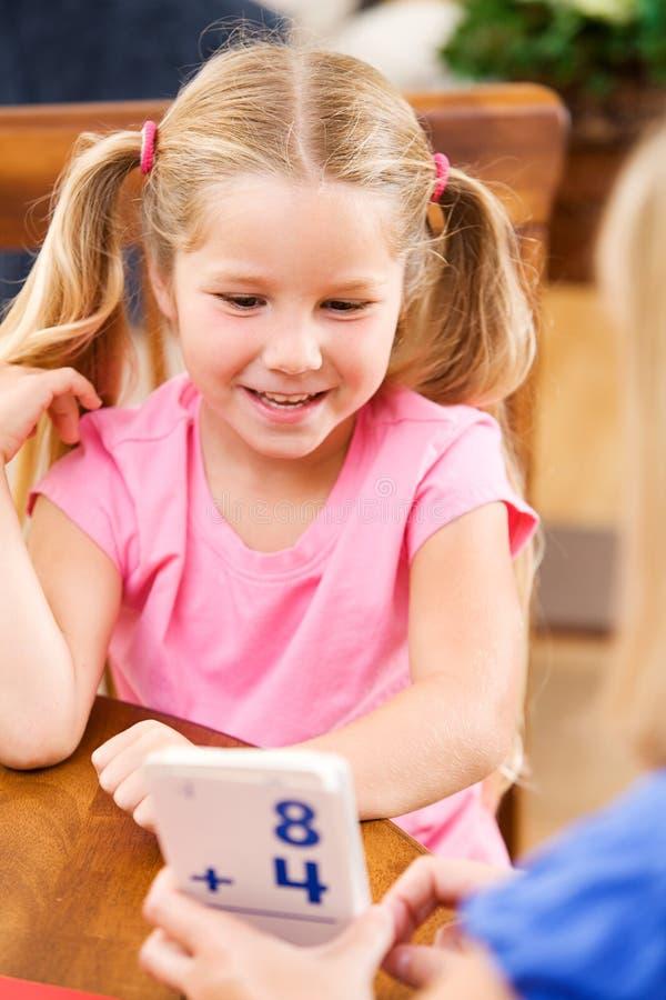 Student: Moderportionbarnet l?r matematik med bildkort royaltyfri fotografi