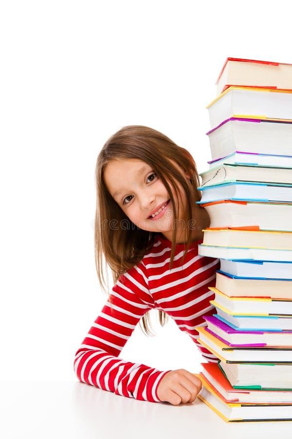 Student och hög av böcker royaltyfria bilder