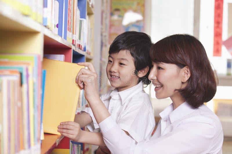 Student och lärare Taking Book från en bokhylla royaltyfri foto