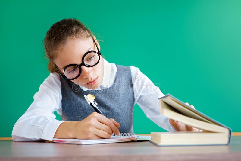 Student peeps into the book, writing off something. stock image
