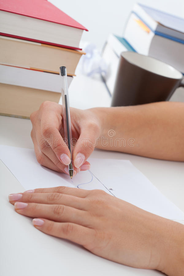Student in physics during learning. Student solving the task of physics, with coffee and stacks of books royalty free stock photography