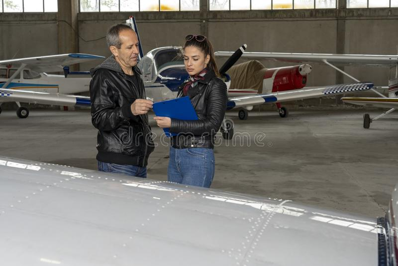Student Pilot och flyginstruktör Check ett flygplan för säkerhet i en hangar royaltyfria bilder