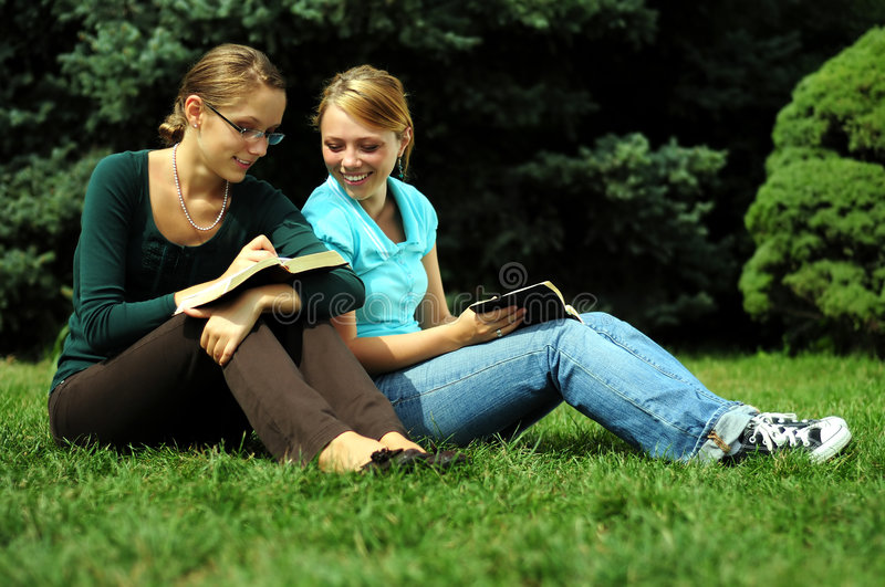 Student Reading. Sisters Reading in a public park stock photo