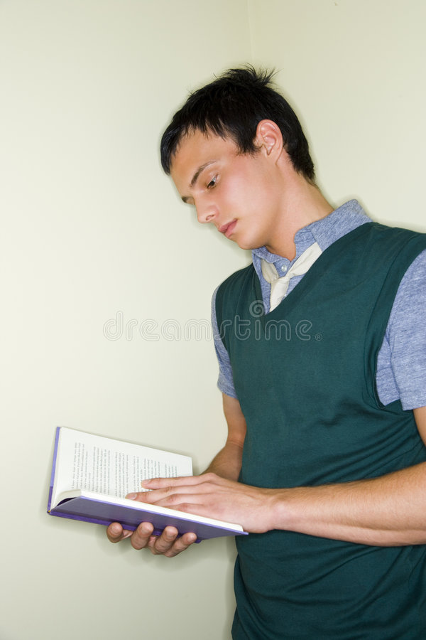 Student reading book. A portrait of a young male student reading a book royalty free stock photo