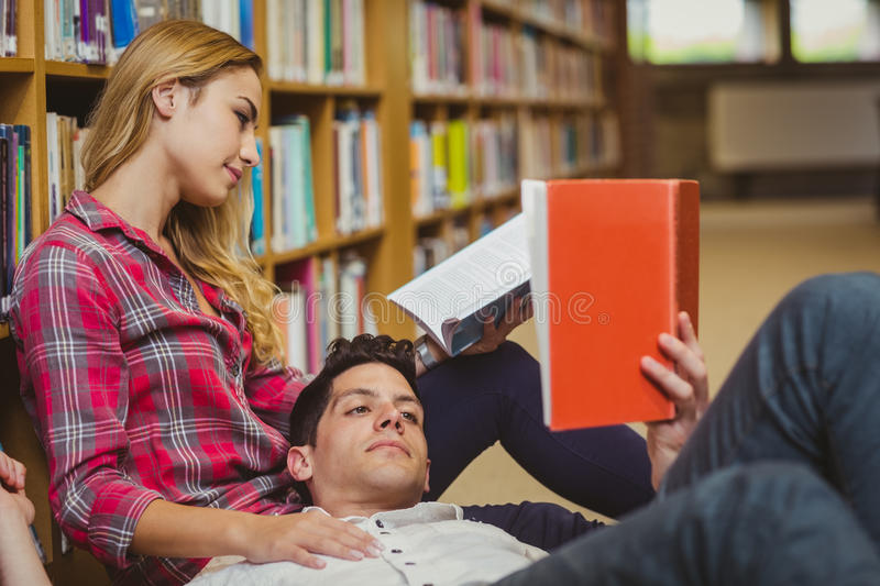 Student reading book while lying on his classmate. In library royalty free stock image