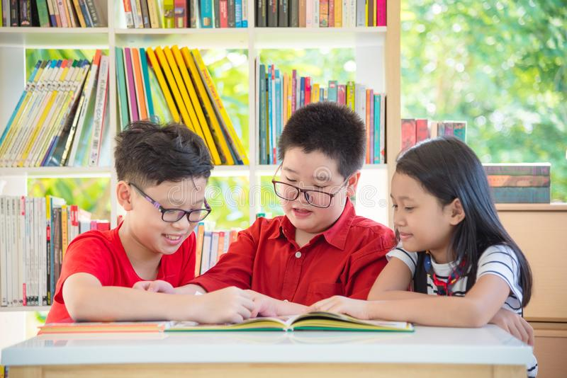 Student reading book together in school library stock photography