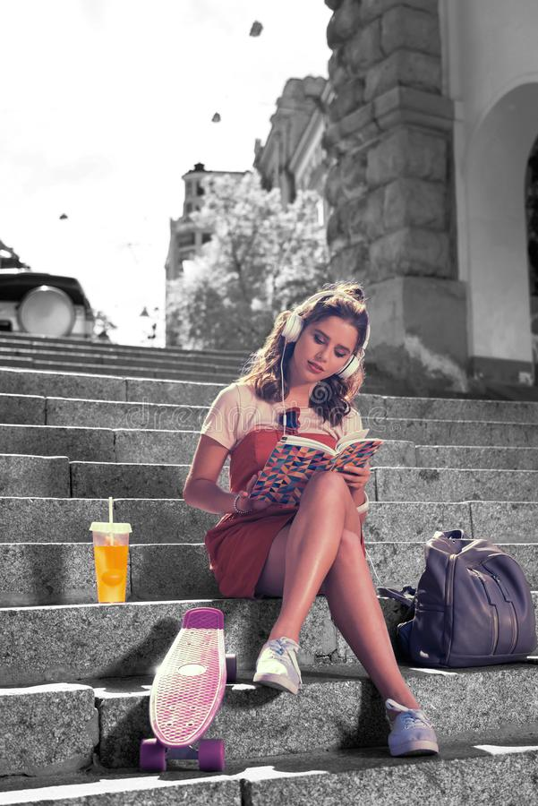 Stylish student wearing white sneakers listening to music in earphones and reading royalty free stock photos