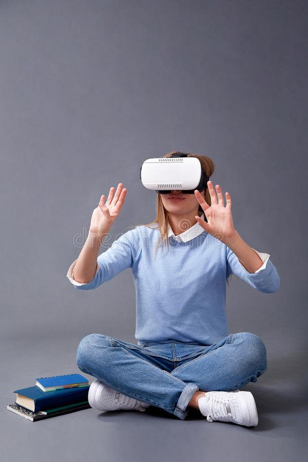 Free Student Reading With VR Glasses Standing On A Gray Background Royalty Free Stock Photography - 143023127