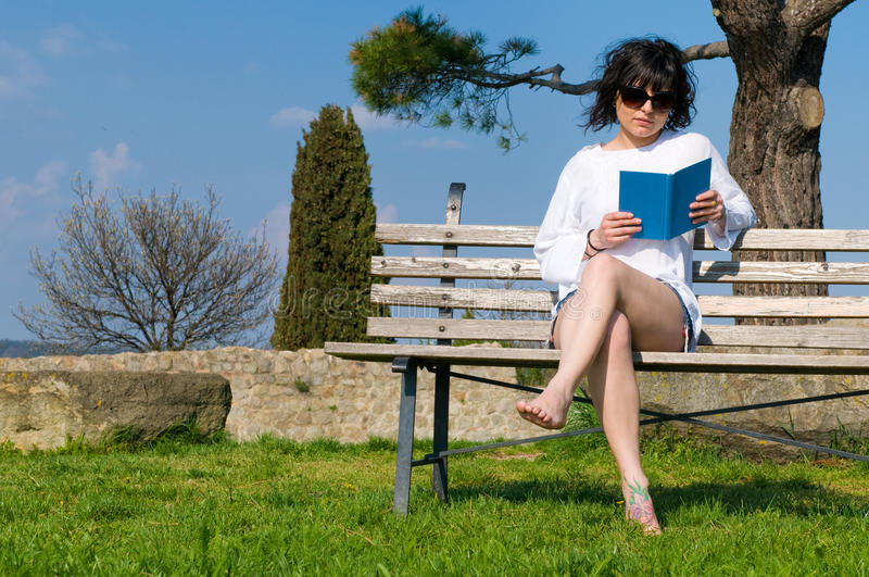 Student Reads The Book Sitting On A Bench Stock Images