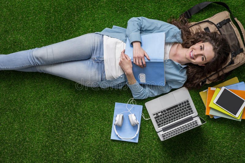 Student relaxing on the grass royalty free stock images