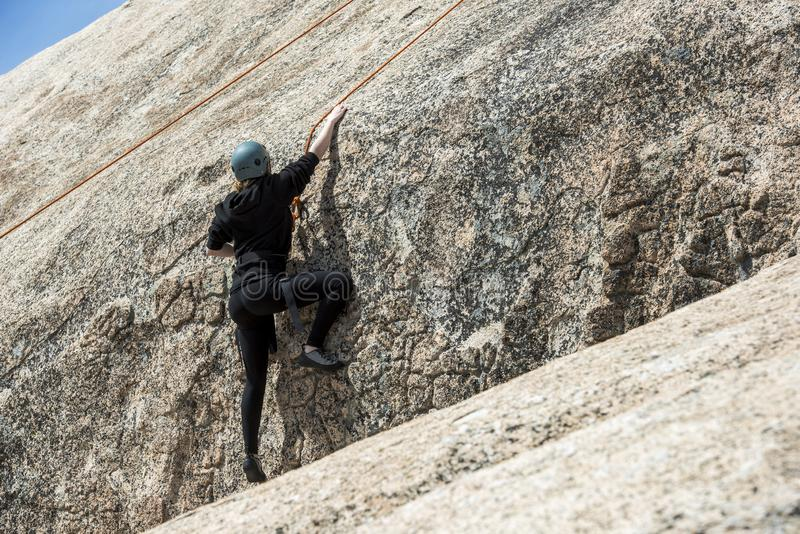 Student rock climber in black stock image