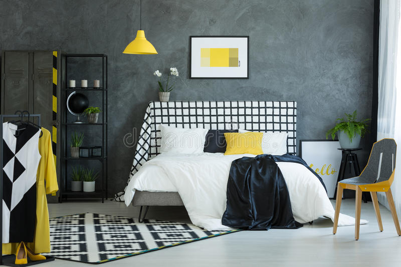 Student`s bedroom with black globe. Simple yellow picture on dark wall in student`s bedroom with black globe on metal shelf royalty free stock photo