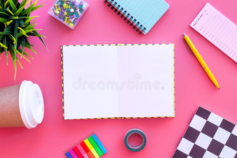 Student`s desk. Notebook, stationery, coffee cup on pink background top view mock up royalty free stock images
