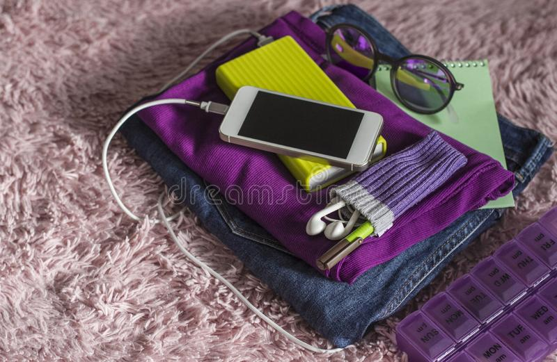Student`s folded things on vacation. Jeans, phone android, poverbank, T-shirt, notebook, pen, Sunglasses, headphones, pill box stock image