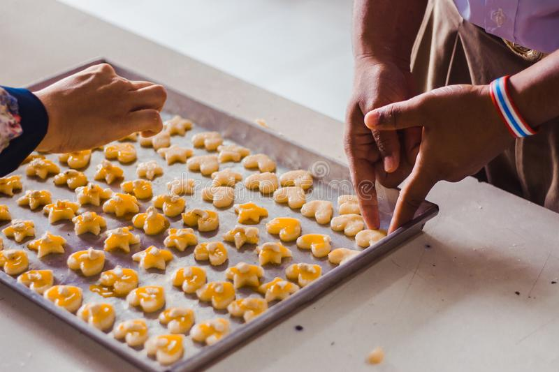Student `s hands make Singapore cookies from dough in school. royalty free stock photo