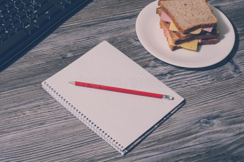 Student`s hard working. Tasty big sandwich on round plate, notebook with pencil, keyboard on gray wooden background. Vintage effe. Ct royalty free stock photo