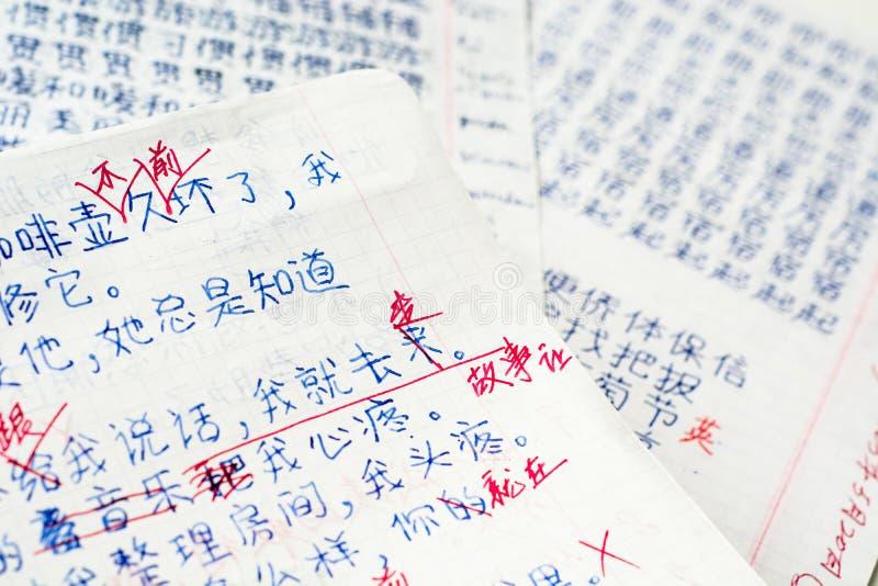 Student ` s Hausarbeit auf Chinesisch mit Korrekturen stockfotografie