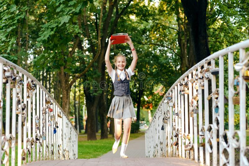Student schoolgirl happy with pigtails in uniform with books in hands above head runs over brid royalty free stock photography