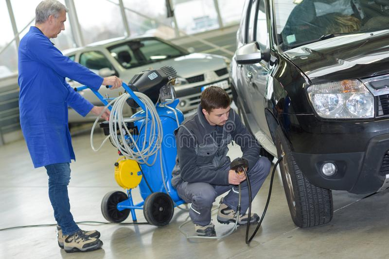 Student and senior mechanic checking tyre pressure at automotive shcool. Mechanic stock photos
