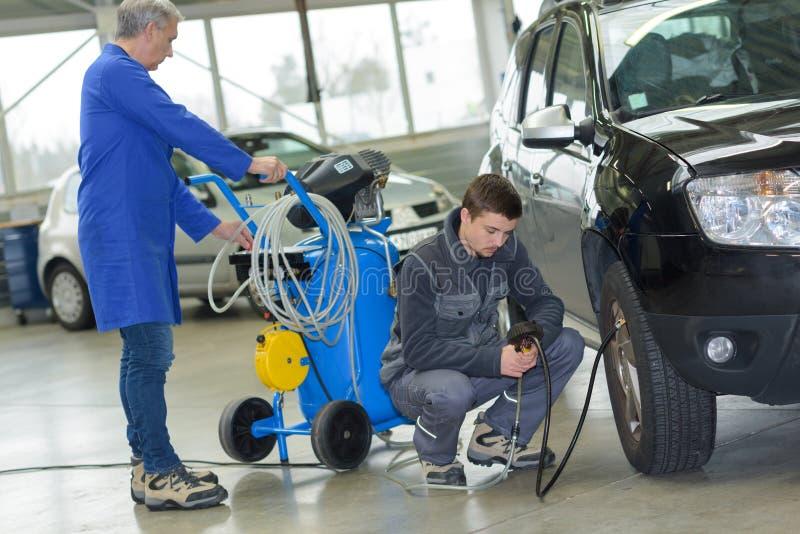 Student and senior mechanic checking tyre pressure at automotive shcool. Mechanic stock image