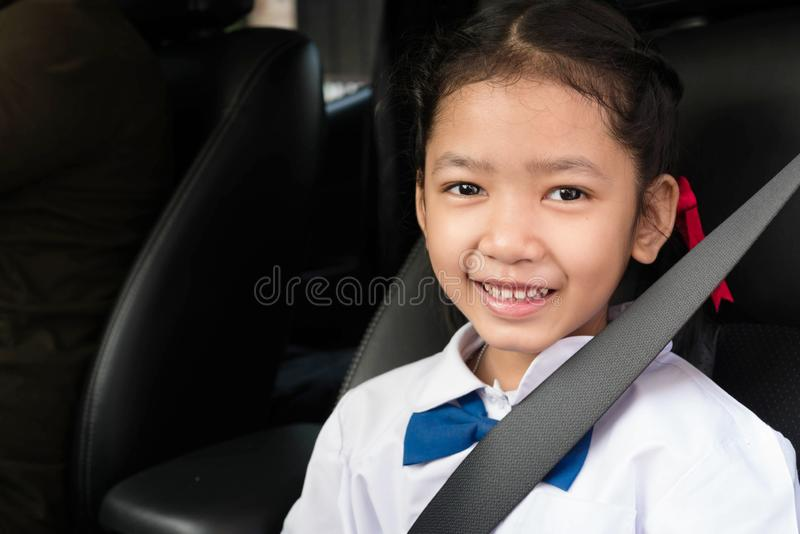 A student sit in the car with smiling. Asian girl wear school uniform sit in the car and fasten the belt for safety. The students sitting with the parents seat royalty free stock images