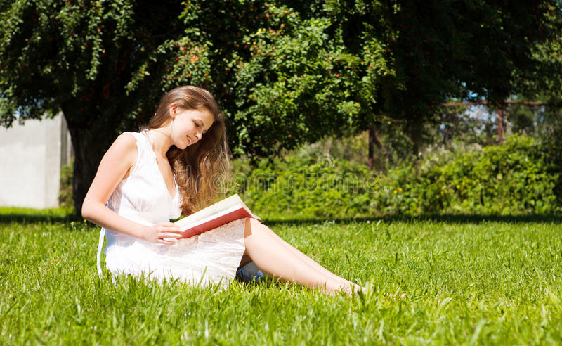 Download Student Sit On Lawn And Reads Textbook Stock Photo - Image: 21230640