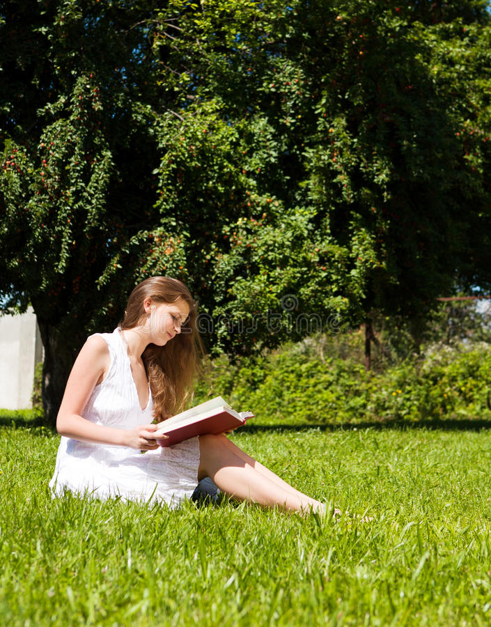 Student Sit On Lawn And Reads Textbook Royalty Free Stock Image