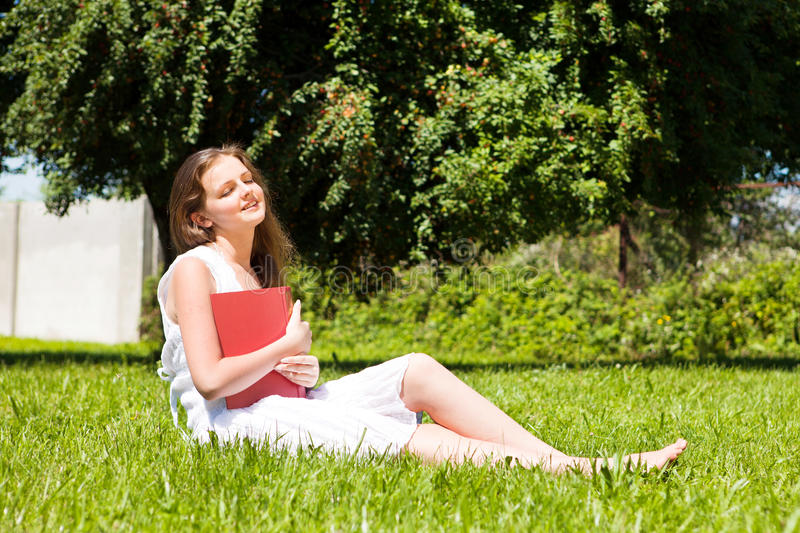 Download Student Sit On Lawn And Reads Textbook Stock Image - Image: 21230705