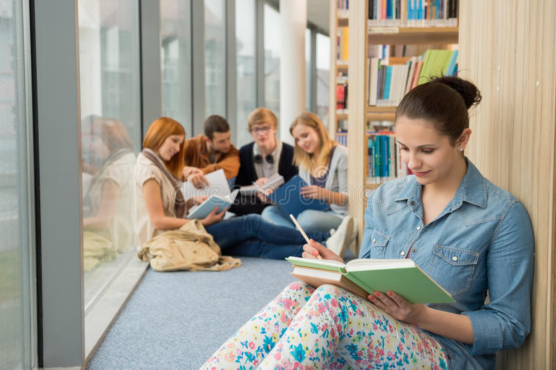 Student sitting in college library with friends royalty free stock photography