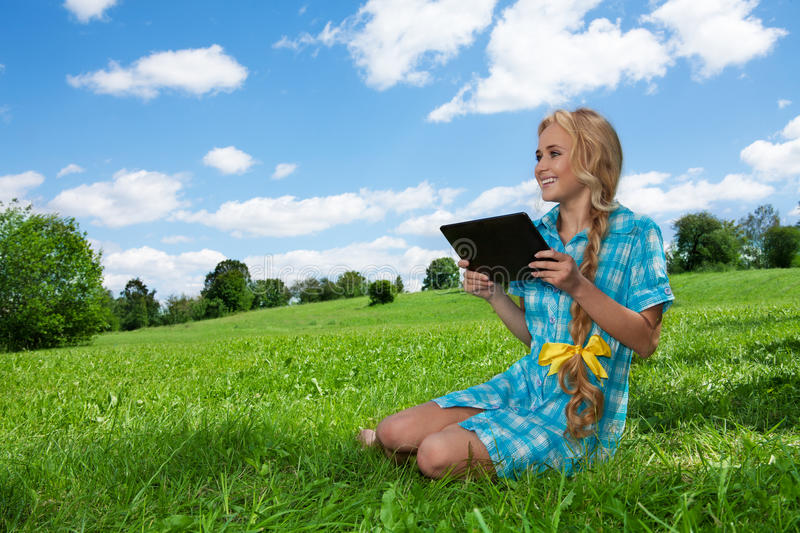 Student sitting on grass browsing stock images