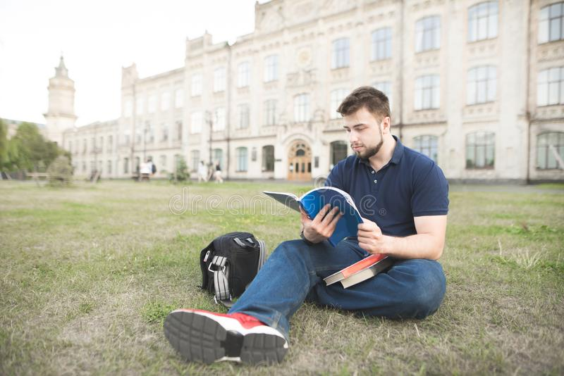 Student sitting on a grass at a university campus and reading a book. Portrait of a student sitting on a grass at a university campus and reading a book. Man royalty free stock photo